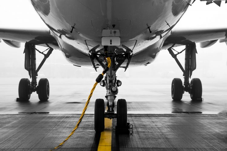 An aircraft parked on the runway with landing gear, tires and a cable around the wheel dock-docking