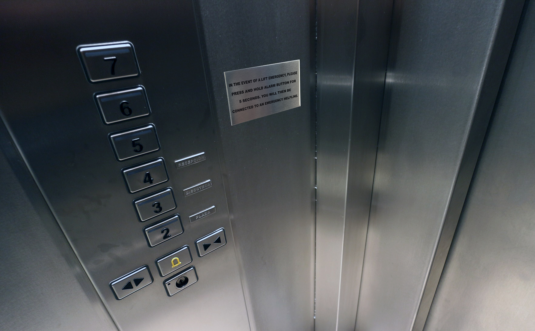Metal warning name plates in a lift elevator