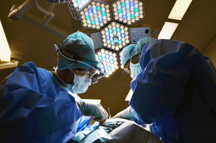 A medical operation with 2 surgeons. Looking up at lights.