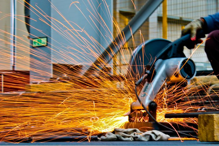 Industrial manufacturing. Sparks while cutting metal bars. Industrial controls panels and systems are designed to keep the workers safe.
